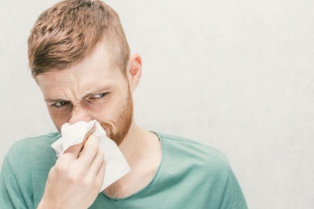 若い男が紙ナプキンを吹き飛ばしています。コンセプト鼻炎