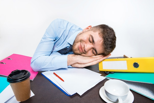 The young man is brazenly sleeping on the desktop during his working hours