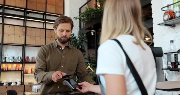 若い男が喫茶店で持ち帰り用のコーヒーを購入し、スマートフォンで非接触型決済を行っています。現代のテクノロジーと銀行のコンセプト。