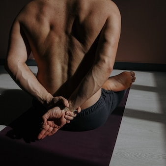 A young man is doing yoga in a fitness studio.