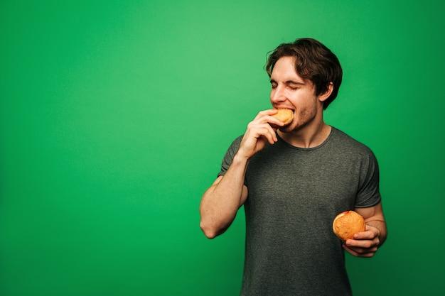 젊은 남자가 기쁨으로 도넛을 먹고있다
