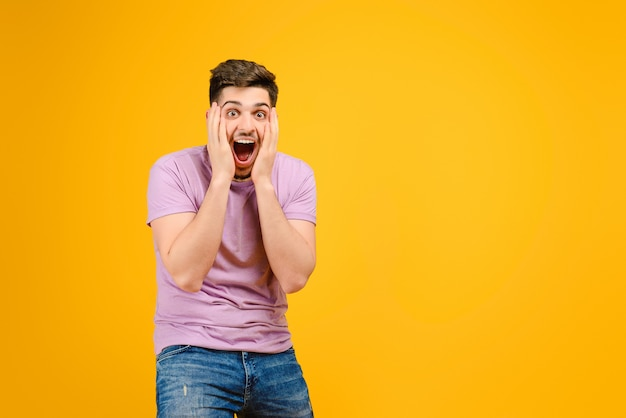 Young man is happy and excited isolated over yellow background