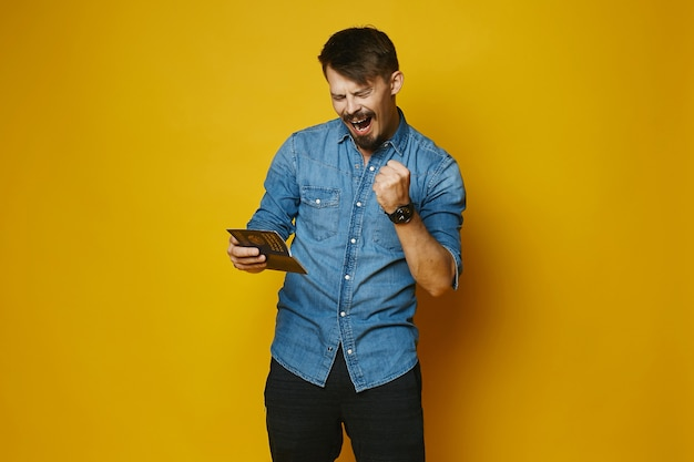 Young man is happy to get a visa in passport, stylish hipster with beard and mustache in fashionable jeans shirt at the yellow , isolated