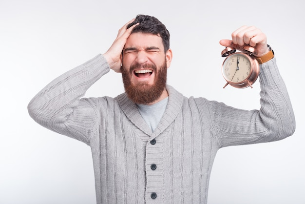 Young man is having headache while holding a clock near white background.