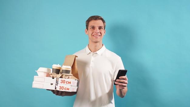 Молодой человек держит в руке коробку с пиццей и кофе, а в другой - смартфон
