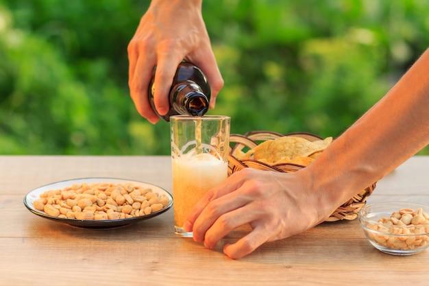 젊은 남자가 맥주 한 병을 들고 유리를 채우고 있습니다. 고리버들 바구니에 감자 칩, 접시와 그릇에 땅콩과 함께 나무 테이블에 유리에 맥주를 붓는 남성 손