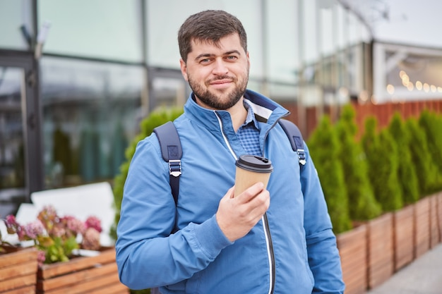 Young man is holding paper cup of takeaway coffee in hands while walking outdoors.