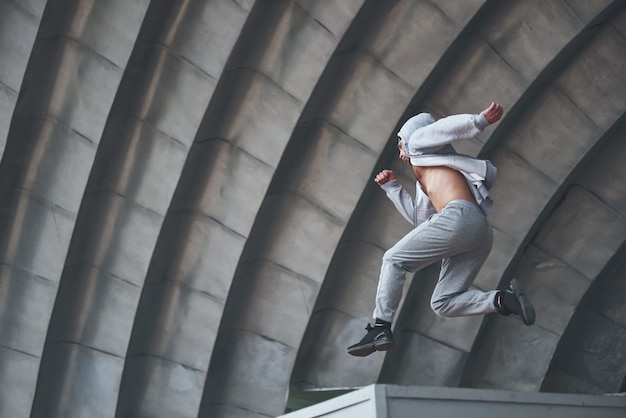 A young man is jumping. parkour in urban space, sporting activity.