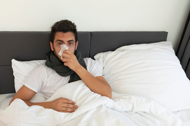 A young man is lying in bed. he is sick, has a high body temperature, runny nose and cough.