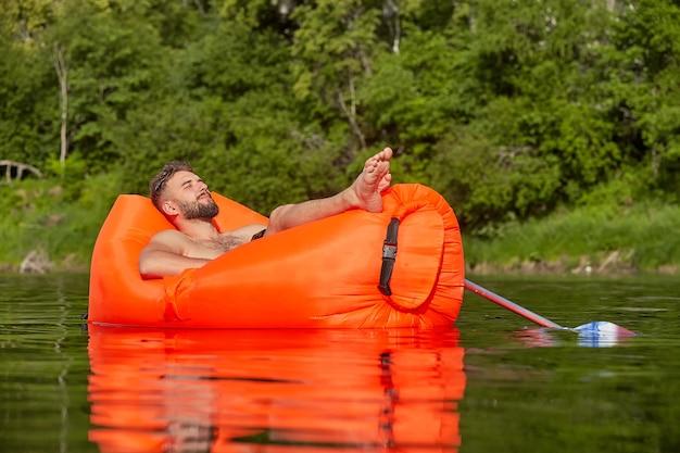 若い男が川に浮かぶオレンジ色のエアソファで昼寝しています。