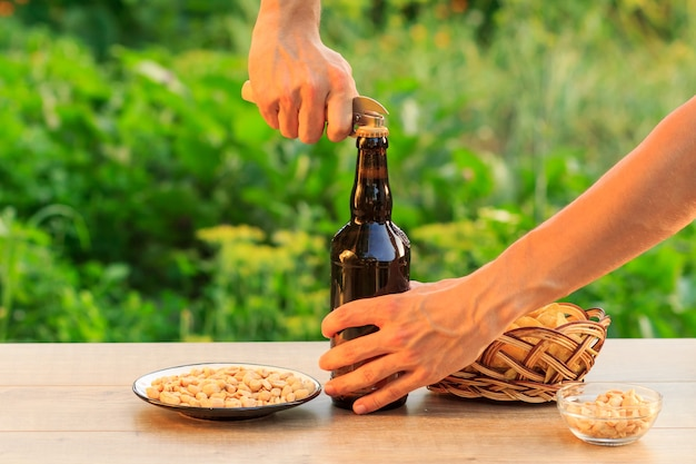 Young man is opening bottle of beer with old opener. brown bottle of beer with potato chips in wicker basket, peanuts in plate and bowl on wooden table