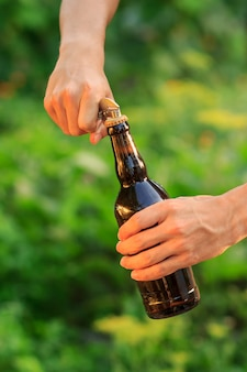 Young man is opening bottle of beer with old opener on natural blurred background