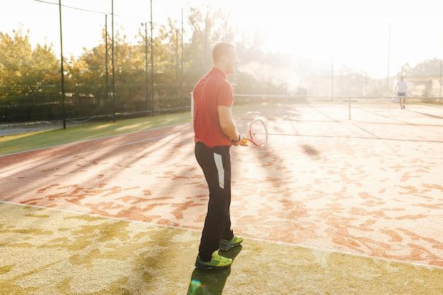 若い男は新鮮な晴れた朝にテニスをしています。