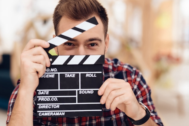 A young man is posing on a camera with a movie clapper.