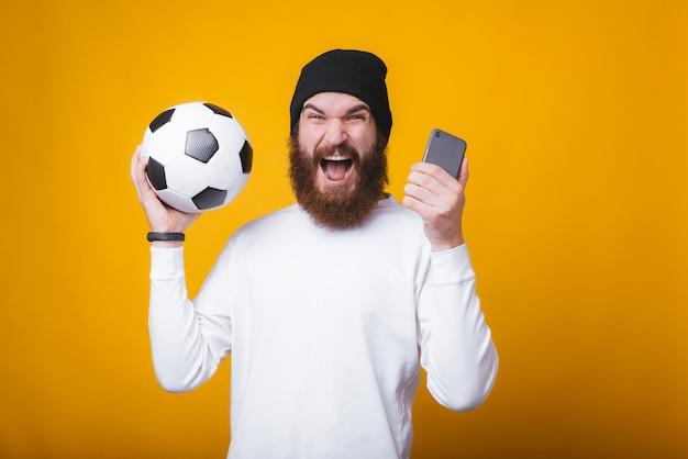 Молодой человек кричит и держит телефон и футбольный мяч возле желтой стены.