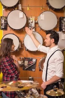 Young man is showing girl drums in the music store.
