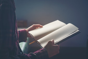Young man is sitting and reading a book .