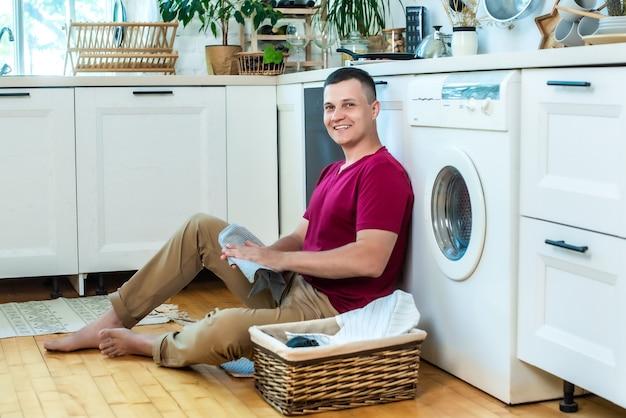 젊은 남자는 세탁기 근처 부엌에서 집에 앉아서 웃고 있습니다. 세탁의 개념은 쉽습니다. 세탁 바구니 옆.