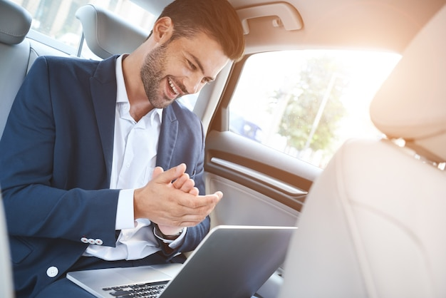 A young man is sitting in the car and enjoying the successful transaction