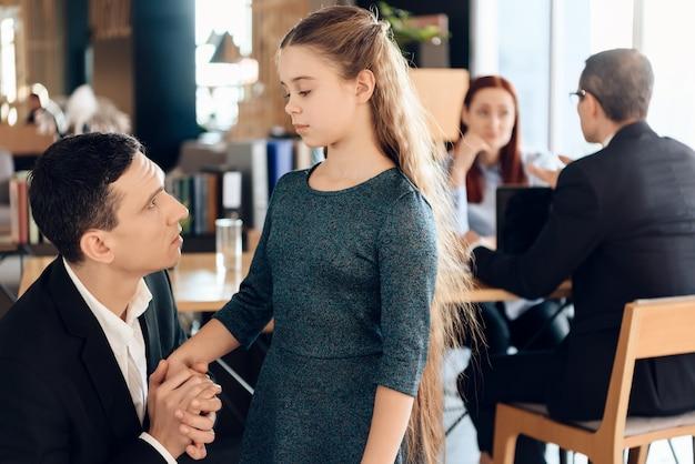 若い男は前景に座っていると女の子を手に保持しています。