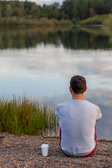A young man is sitting on the shore of the lake and looking into the distance, next to a white mug of coffee or tea. solitude and relaxation in nature. a beautiful landscape of a lake in the forest