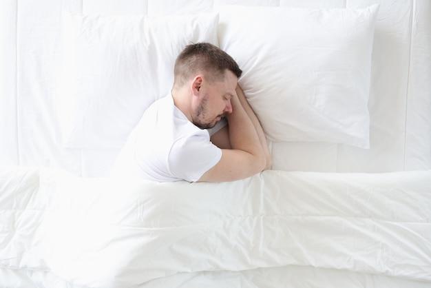 젊은 남자가 큰 흰색 침대에서 평화롭게 자고있다.