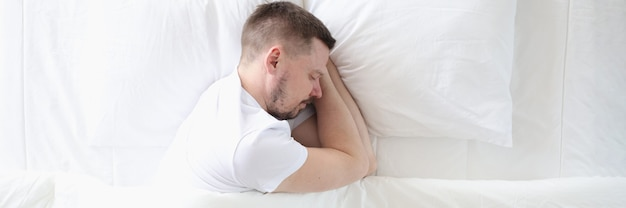 Young man is sleeping peacefully on large white bed healthy sleep concept