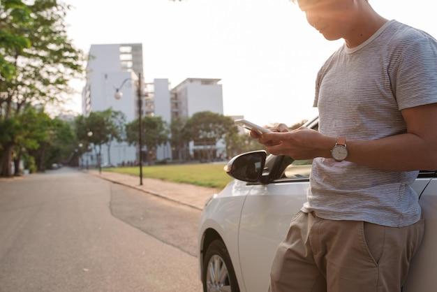 젊은 남자는 전기 자동차 근처에 서서 스마트 폰을 봅니다. 렌트카가 전기차 충전소에서 충전을 하고 있다. 카 셰어 링.