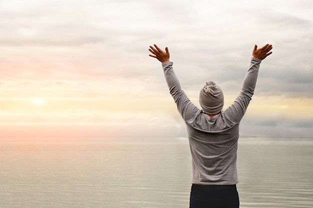 A young man is standing on the shore. the view from the back. yoga classes. hands raised up. freedom and achievement.