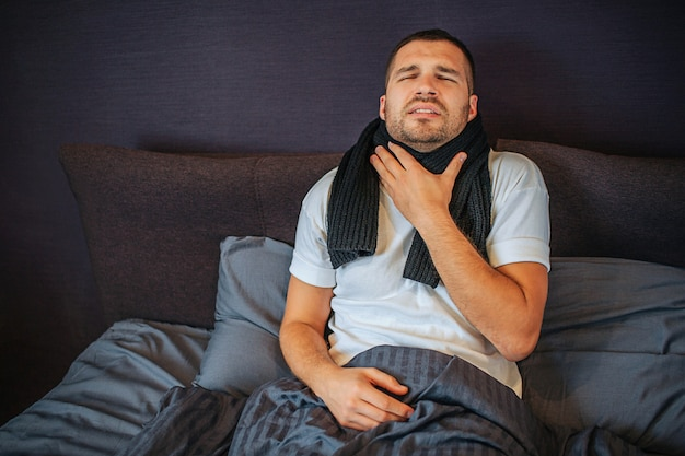 Young man is suffering from strong throat pain. he holds hand close to scarf and shrinks. guy shrinks and keeps eyes closed. pain is terrible.
