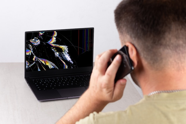 A young man is talking on a mobile phone in front of a laptop with a broken, cracked screen