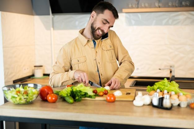 젊은 남자는 부엌에서 샐러드를 요리하는 동안 전화 통화입니다. 비건 남자가 샐러드를 위해 야채를 자르고 있습니다.