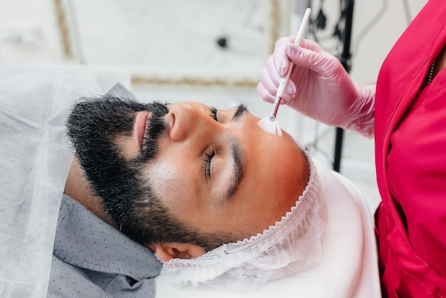 A young man is undergoing a cosmetic facial peeling procedure. cosmetology and rejuvenation.