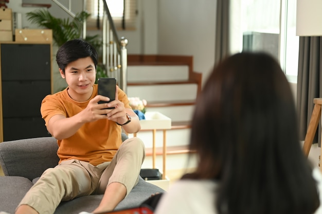 Young man is using smart phone taking photo of his girlfriend on couch in living room