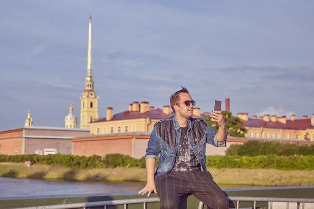 若い男は、ロシアのサンクトペテルブルクの歴史的中心部に座っている間、スマートフォンの画面で見ています。