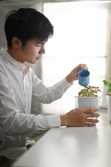 A young man is watering the plant at the white working table