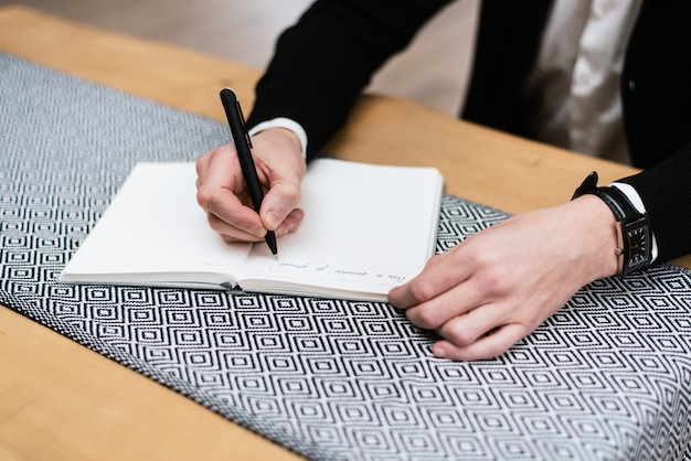 A young man is working in his office. the teacher prepares for the lecture. designer hand working in notebook on wooden desk in office