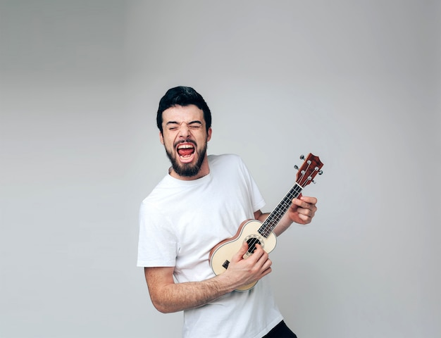 Young man isolated over background playing on ukulele