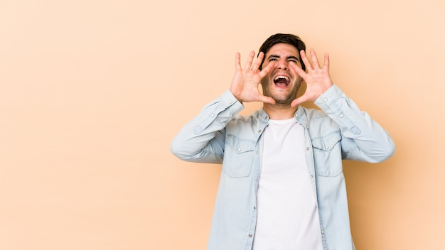 Young man isolated on beige shouting excited to front.