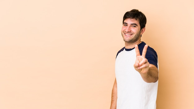 Young man isolated on beige space showing victory sign and smiling broadly.