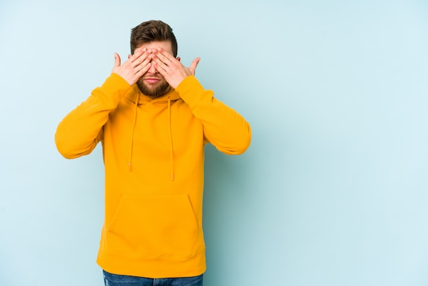 Young man isolated on blue wall afraid covering eyes with hands