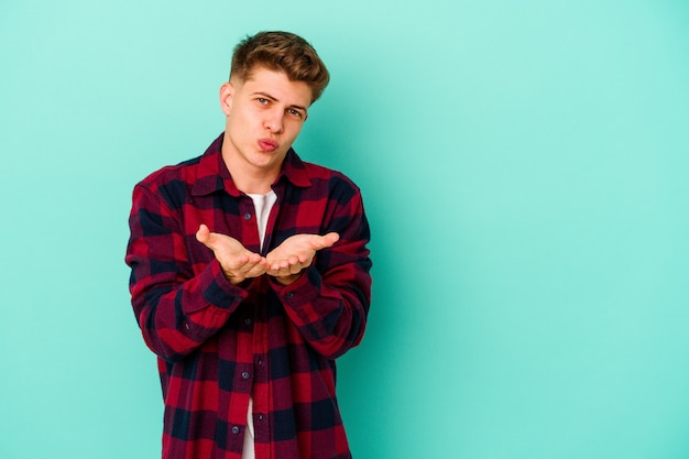 Young man isolated on blue wall folding lips and holding palms to send air kiss