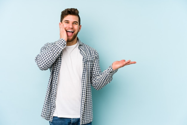 Young man isolated on blue wall holds copy space on a palm, keep hand over cheek amazed and delighted.