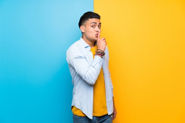 Young man over isolated colorful  doing silence gesture