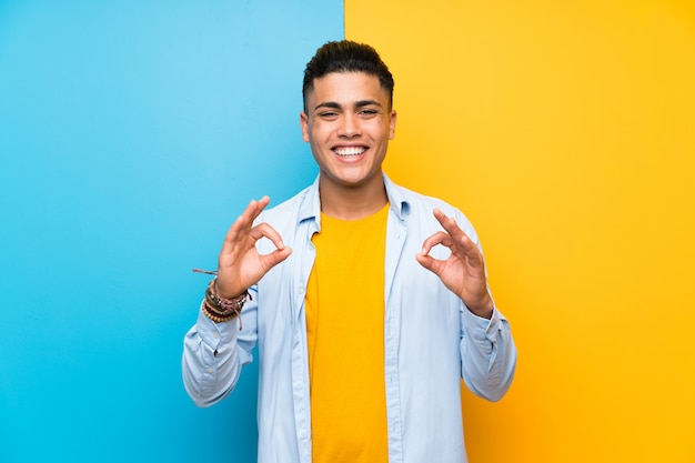 Young man over isolated colorful wall showing an ok sign with fingers