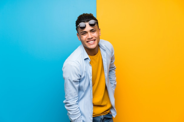 Young man over isolated colorful wall with sunglasses