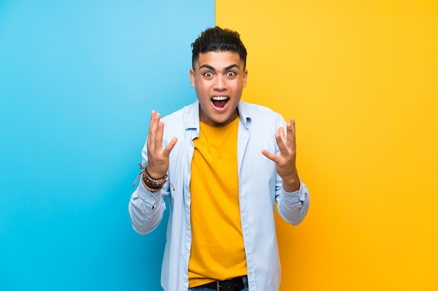 Young man over isolated colorful  with surprise facial expression