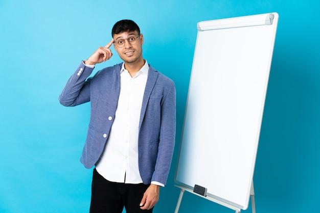 ホワイトボードでプレゼンテーションを行い、解決策を実現しようとしている青で孤立した若い男