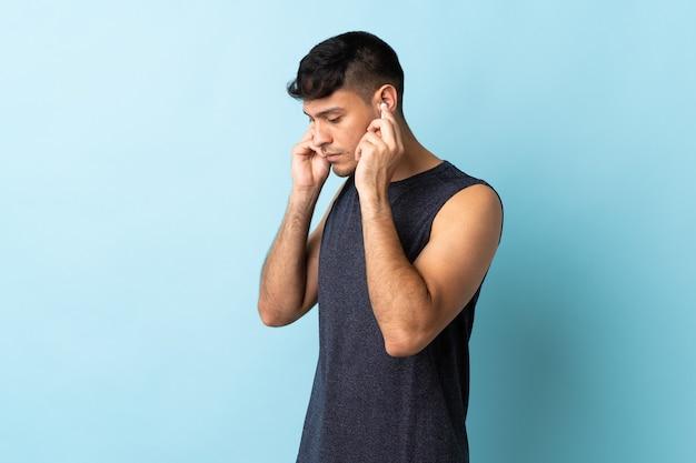 Молодой человек изолирован на синем прослушивании музыки