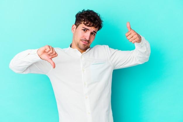 Молодой человек изолирован на синей стене показывает палец вверх и палец вниз, трудно выбрать концепцию